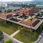 Elevated Concrete Pathway on Stilts Shades Brick Training Centre in Hanoi